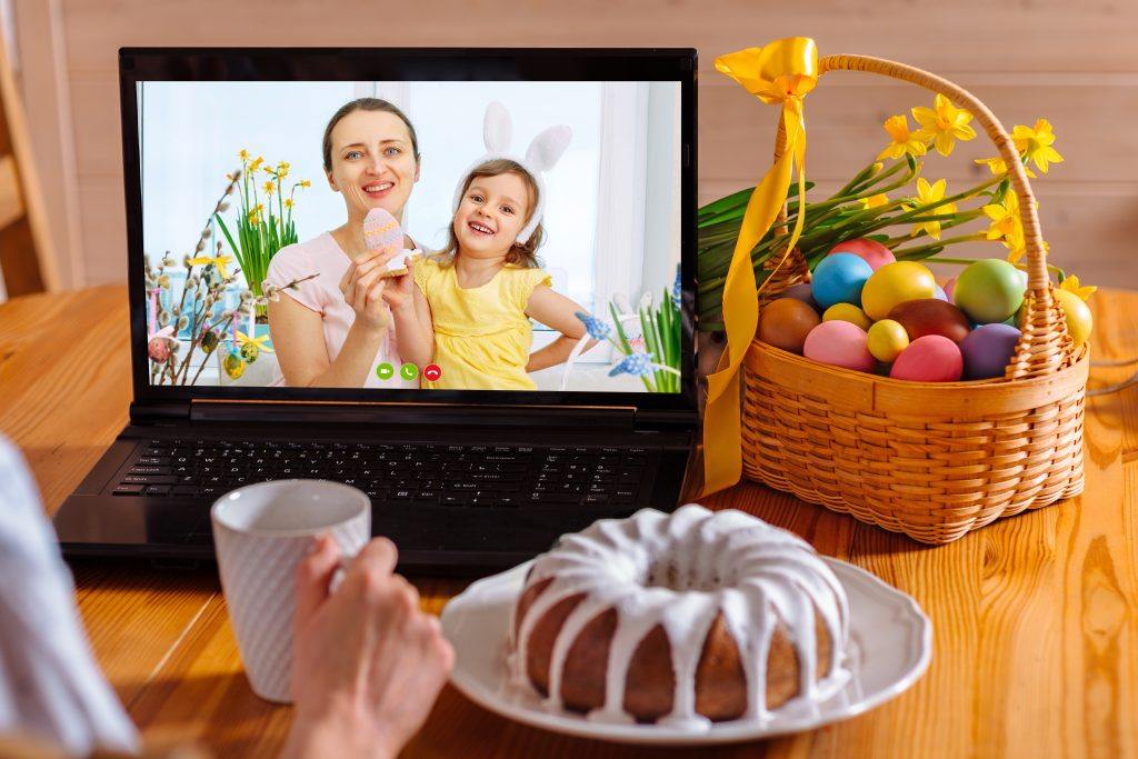 A mother and her daughter are talking via video link to their friends. Decorated table with flowers and a basket with colorful eggs and cake. Chatting during the COVID pandemic and the Easter holidays