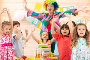 Clown playing with children. Kids group celebrate birthday and pose for camera standing with hands up at table. Holiday in a children's club.