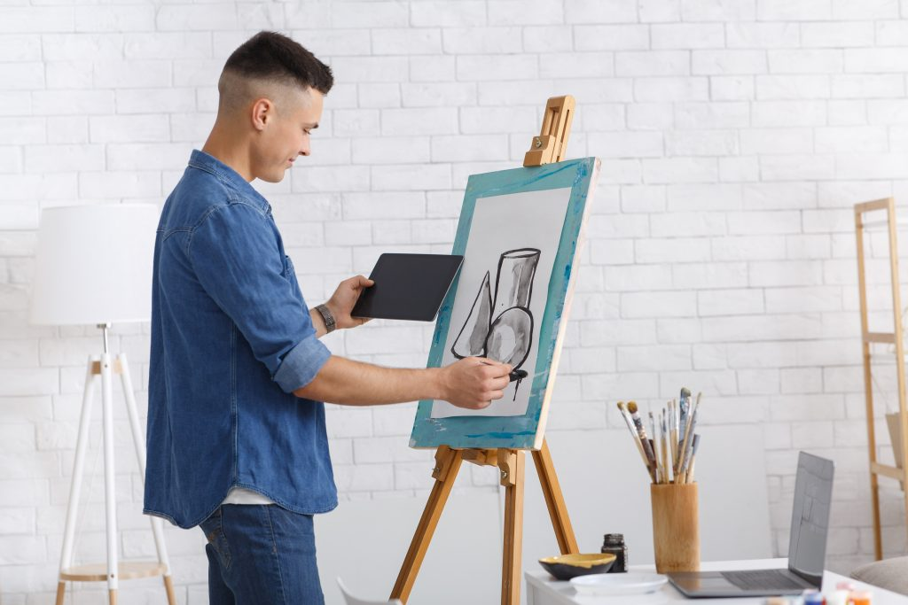 First painting lessons online at home during self-isolation at outbreak of coronavirus. Millennial man looking at tablet and drawing picture on easel at home with brushes and laptop on table, copy space