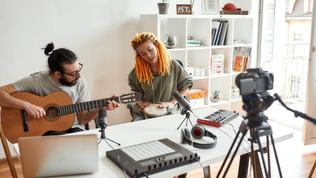 Music is art. Man playing guitar and woman playing rhythm with djembe drum while recording video blog or vlog. Couple of musicians making music at home. Blogging, music, creation. Web Banner