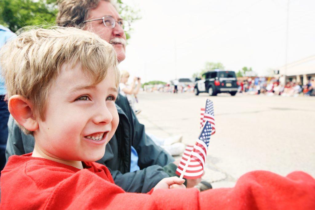 Father and son at Memorial Day parade, watching Memorial Day parade