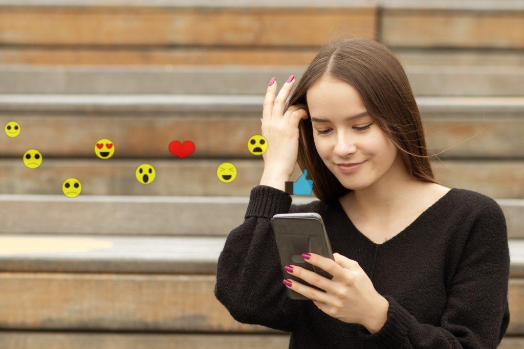 teenager girl using smartphone sending emojis, watching video live streaming, emojis, teenager texting with emojis, texting with emojis