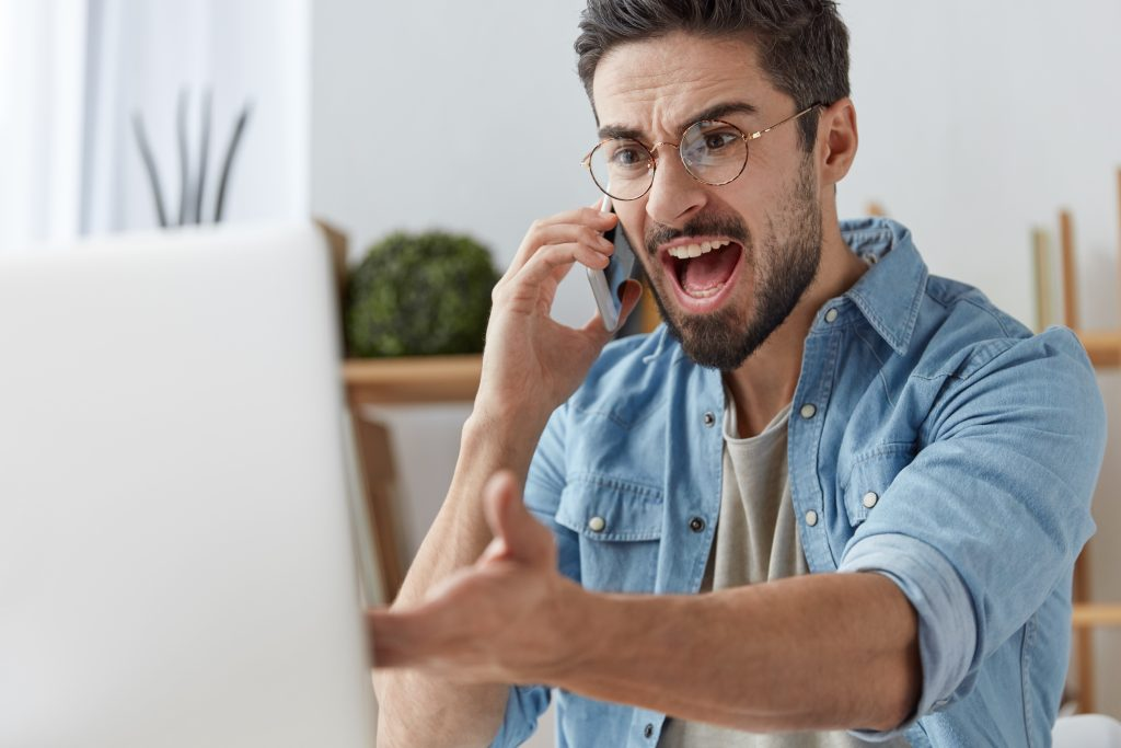 Annoyed brunet unshaven male has quarrel with colleague on smart phone, looks in irritated expression at laptop computer, can`t solve problem of new application, has some troubles with internet