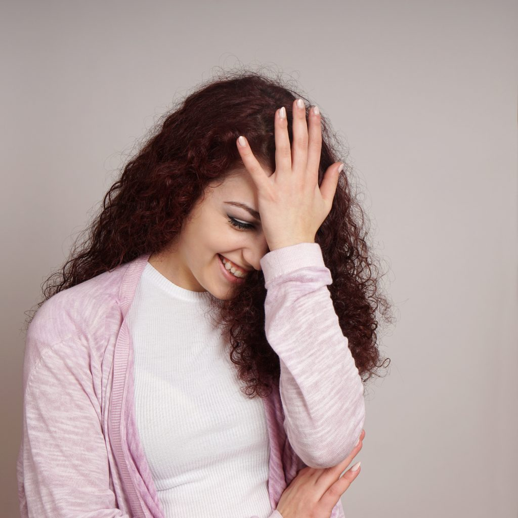 young woman feeling embarrassed with hand on forehead also known as facepalm