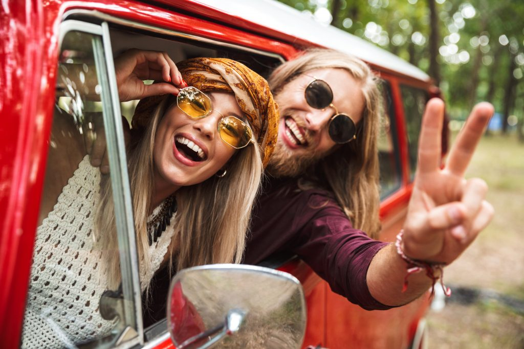 Photo of happy hippie couple smiling and showing peace sign while driving retro minivan in forest