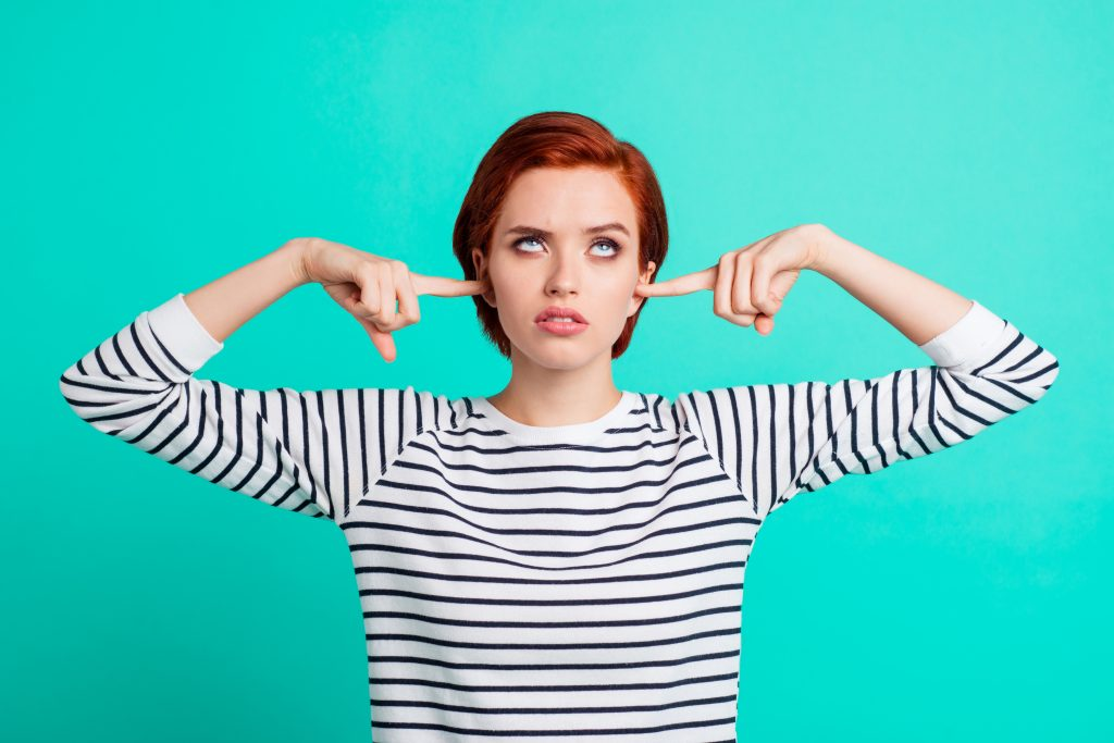 Portrait of nice pretty charming attractive sad red-haired lady wearing striped pullover rolling eyes up closing ears with forefingers isolated over bright vivid shine green turquoise background