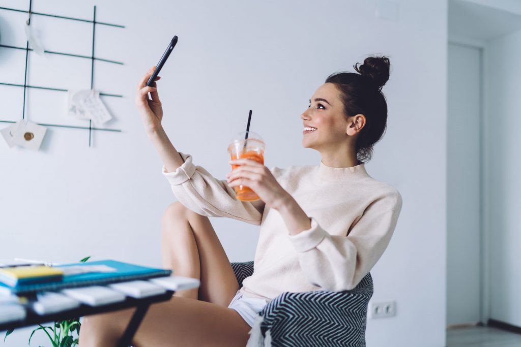 Side view of happy adult female in casual clothes focusing on screen and taking selfie with smartphone while sitting in armchair at desk and holding take away glass with orange drink and straw in light apartment on blurred background