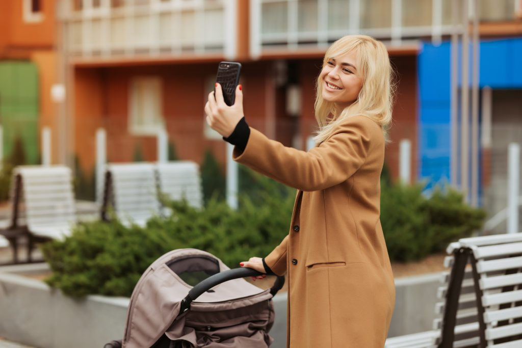 Happy mother walking with her baby in the stroller and taking selfie, mom with blonde hair taking a selfie