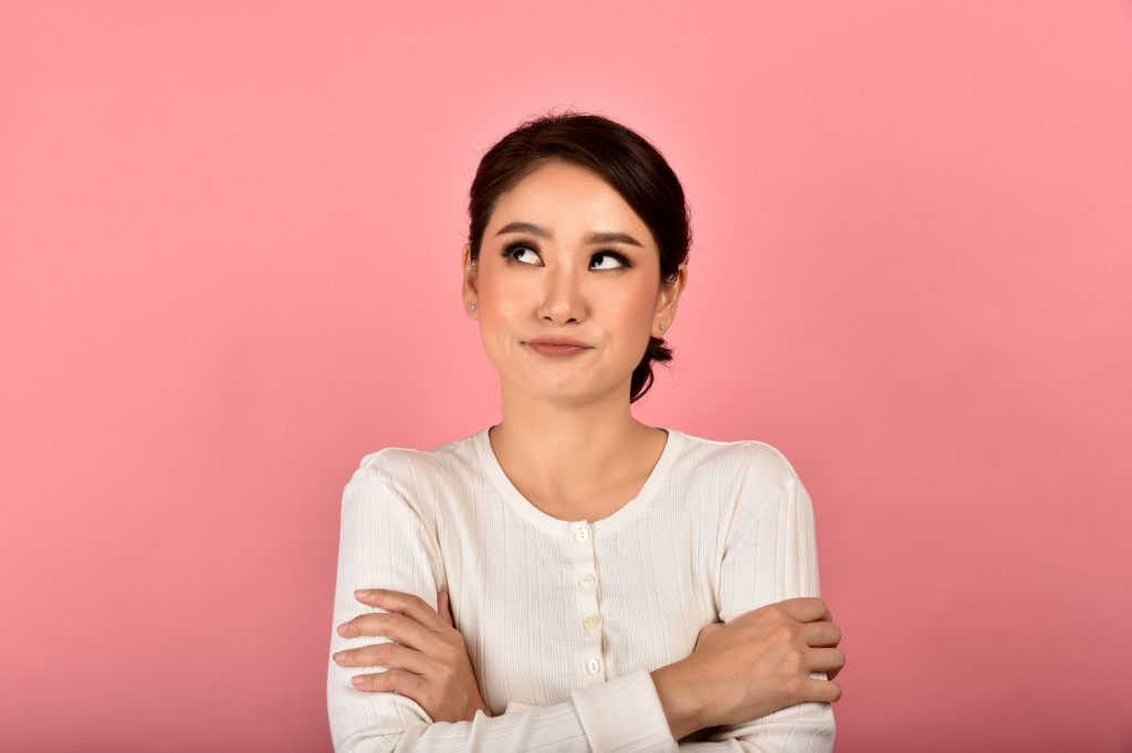 Asian woman feeling upset and frustrated, Girl rolling eyes with boredom and annoy about gossip, Face expression and body gesture.