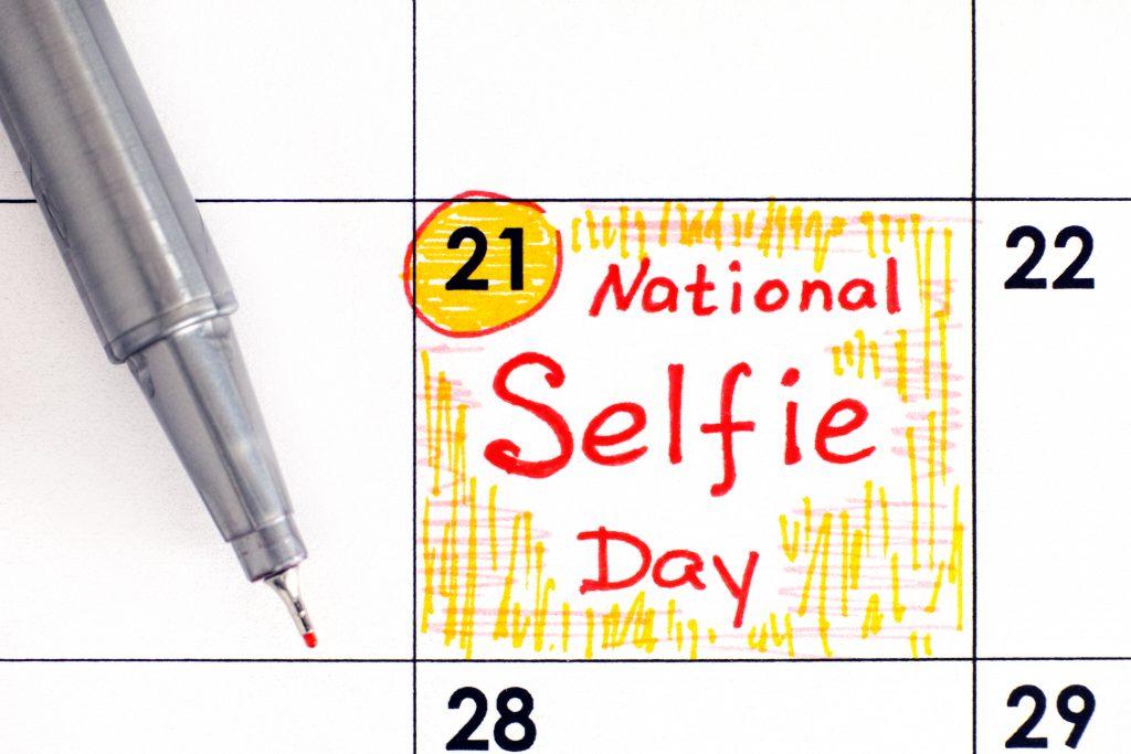 Reminder National Selfie Day in calendar with pen. June 21.