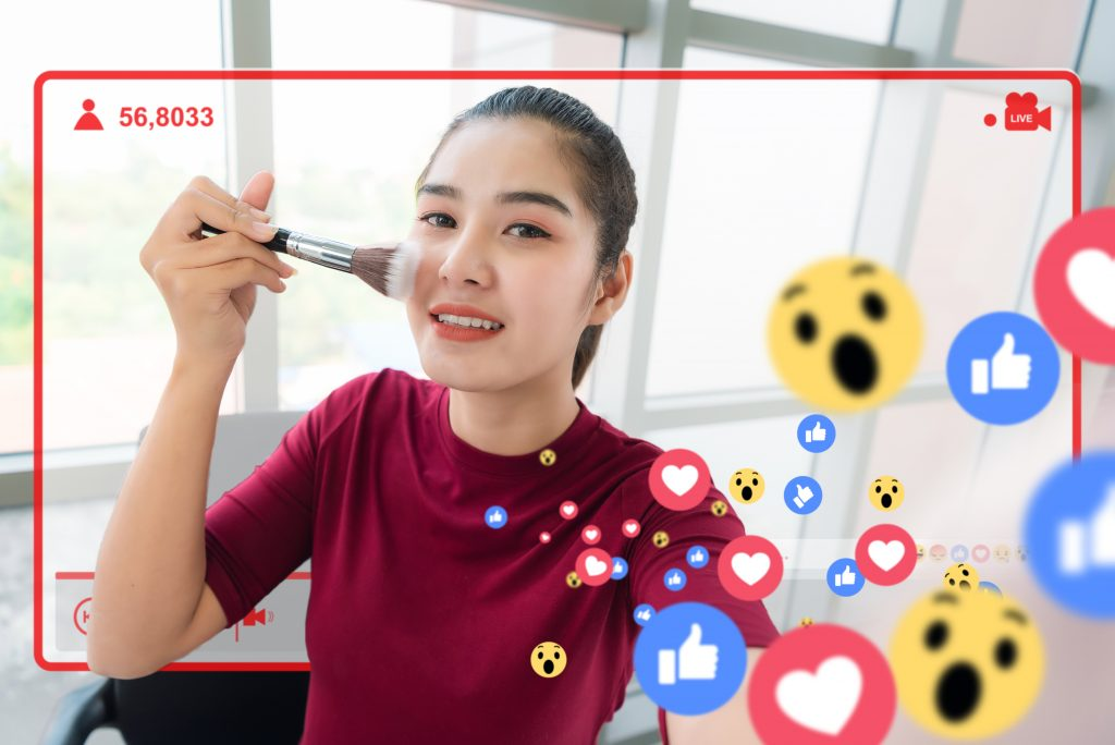 Famous blogger. Cheerful female vlogger is showing cosmetics products while recording video and giving advices for her beauty blog. Focusl camera selfie view