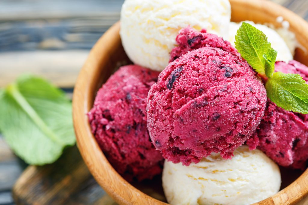 Wooden bowl with homemade lemon and berry ice cream, selective focus.