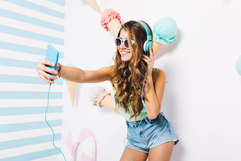 Gorgeous long-haired girl wearing sunglasses and denim shorts making selfie during listening music. Excited young woman posing with happy face expression holding phone on decorated wall.