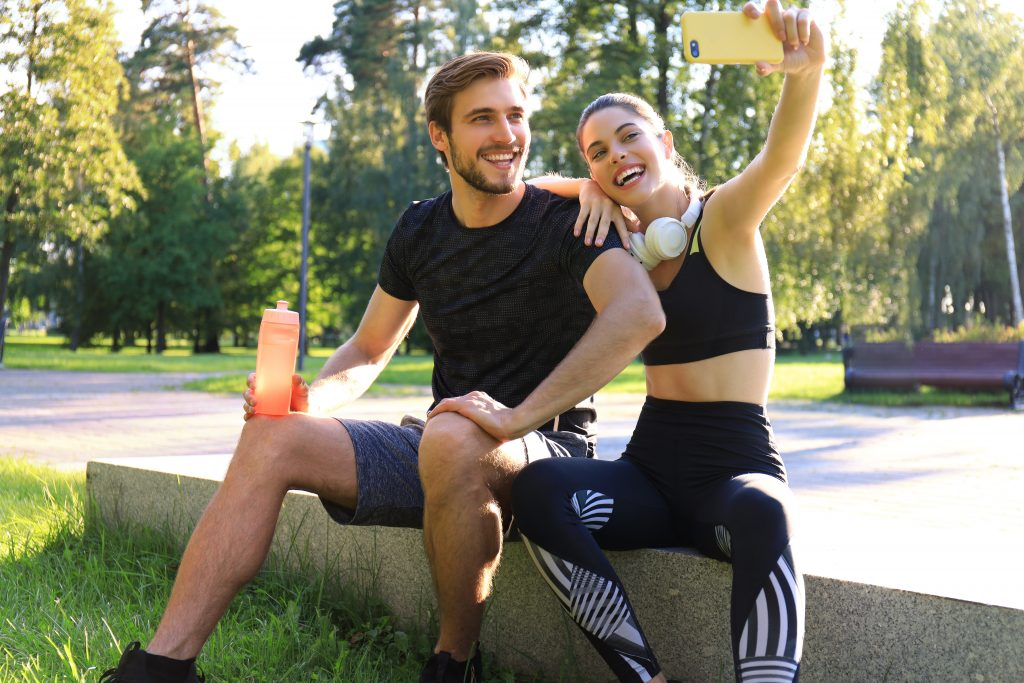 Young sporty couple sitting on parapet in urban park and taking selfie after workout or jog on summer sunny day
