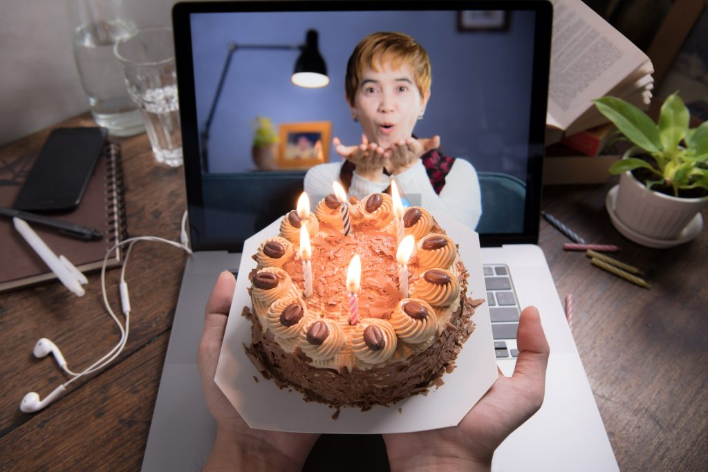 Asian middle aged woman feeling loved and happy while celebrating virtual birthday via video call at home during social distancing