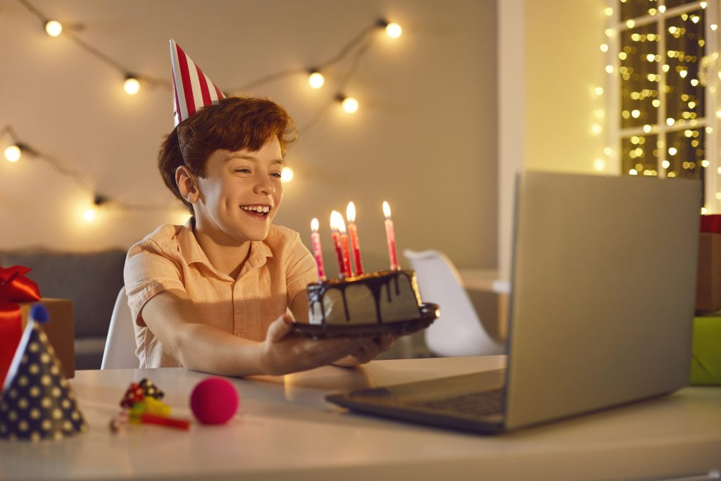 Happy smiling boy sitting at laptop computer, holding his birthday cake with burning candles and showing it to his friends or relatives during video call. Online lockdown party at home concept