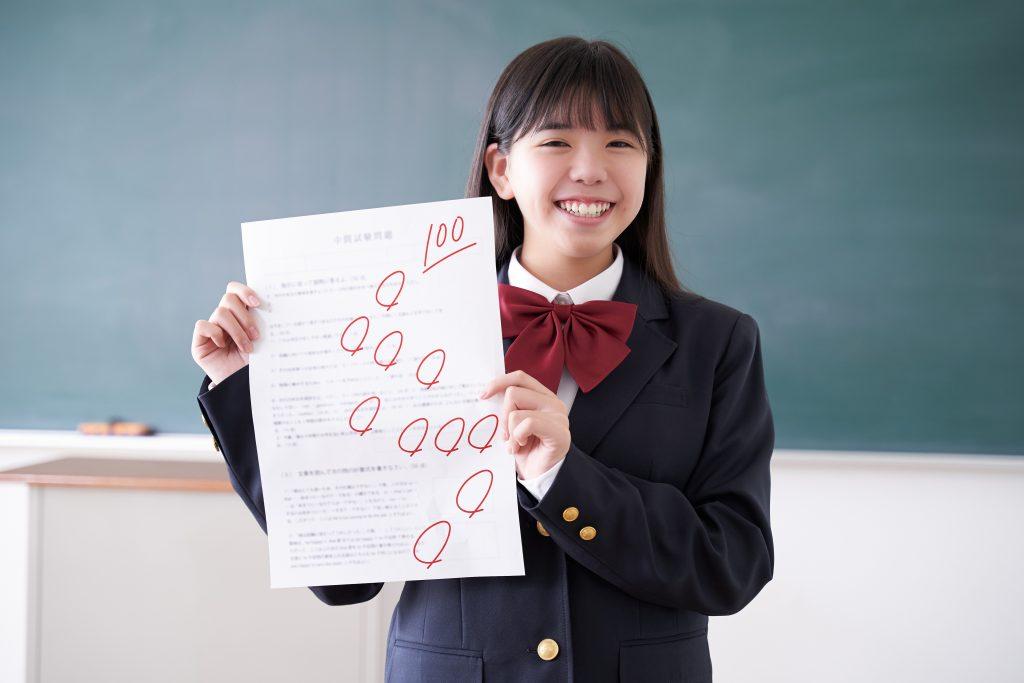 Girl holding exam with 100, 100 emoji