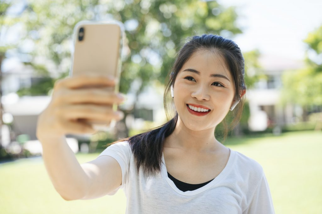 Sporty asian woman vlogging about exercise or selfie with smartphone at park.