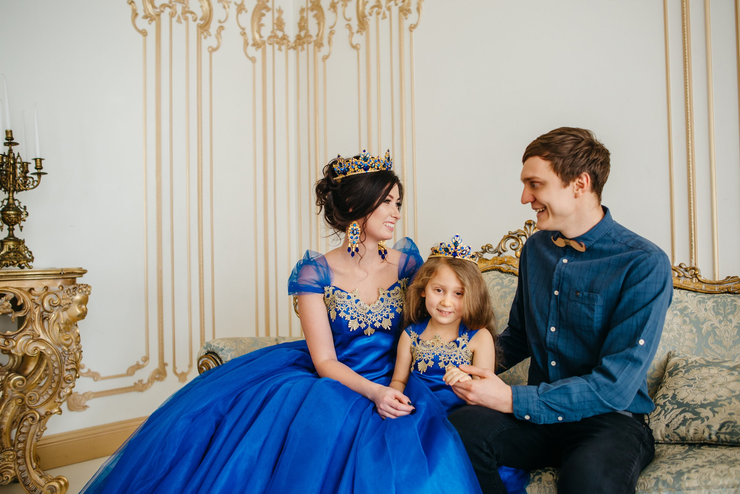 happy young family consisting of mother, father and little daughter in royal attire