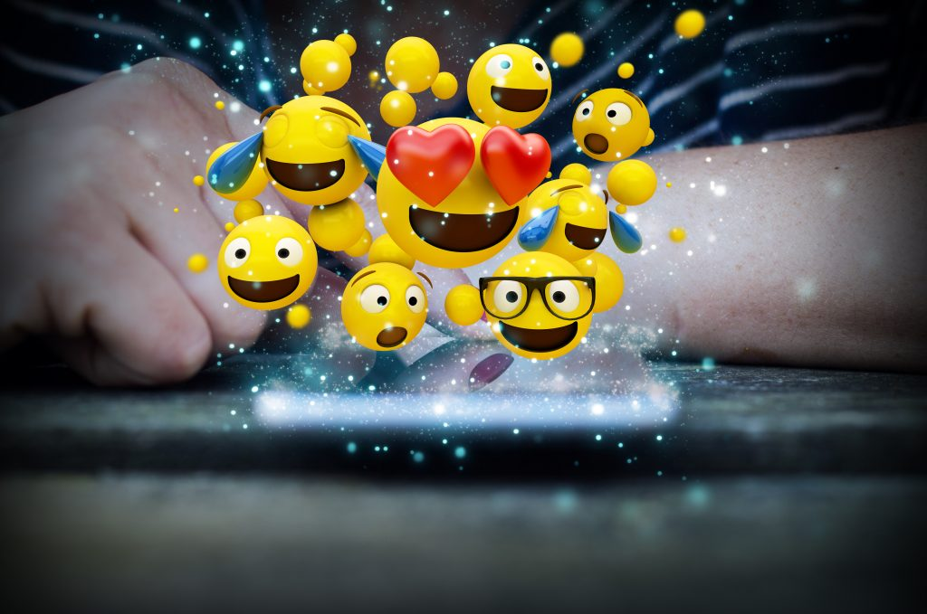 Woman's hand touching a phone with emojis jumping out, emojis jumping out, group of emojis jumping out of a phone