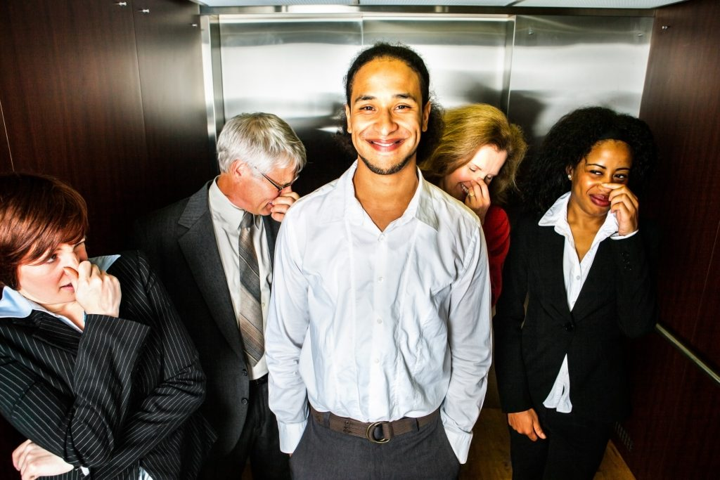 A young man smiles in embarrassment in an elevator while people pinch their noses, man smiling while people smell something foul in an elevator