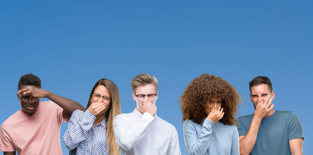 Group of friends holding their nose over a blue background, five friends smelling something unpleasant, five friends covering their noise against a blue background