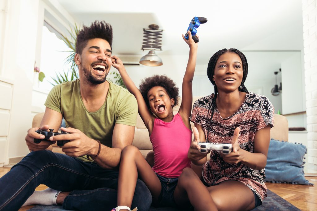 Smiling family playing video games, family playing games at home, smiling family playing games, African American family playing video games