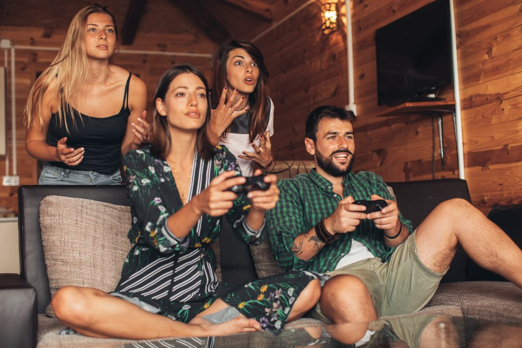 Happy friends playing video games at home, guys and girls playing video games at home
